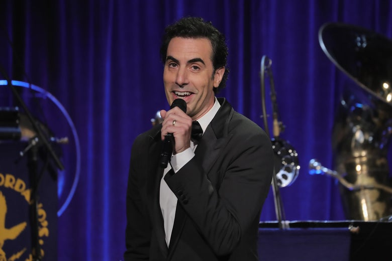 """Sacha Baron Cohen holds a microphone on stage at the Friars Club in New York City. """"Srcset ="""" https: //compote.slate. com / images / e482c225-993f-4b90-8987-33e2729080cf.jpeg? Width = 780 & height = 520 & rect = 3000x2000 & offset = 0x0 1x, https://compote.slate.com/images/e482c225-993f-4b90-8987-33e2729080cf.jpeg? 2x"""