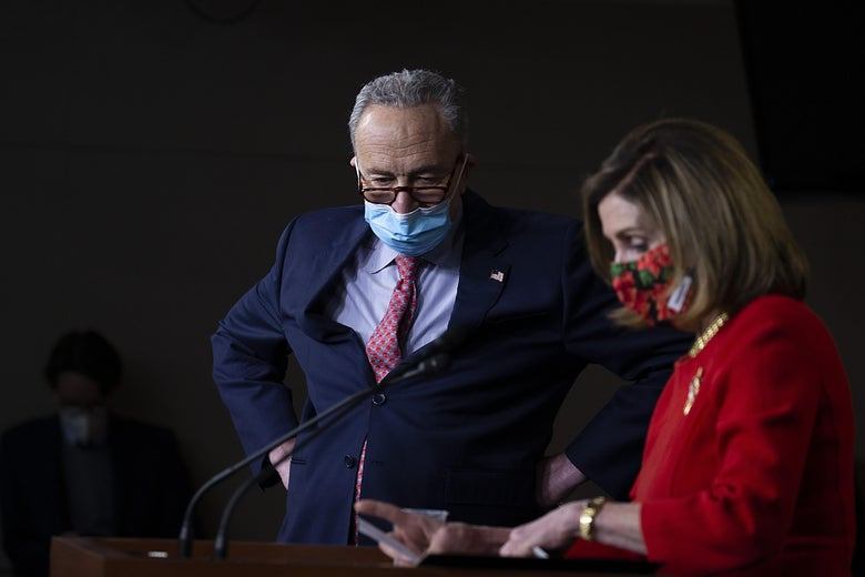 Chuck Schumer and Nancy Pelosi look at a podium while wearing masks.