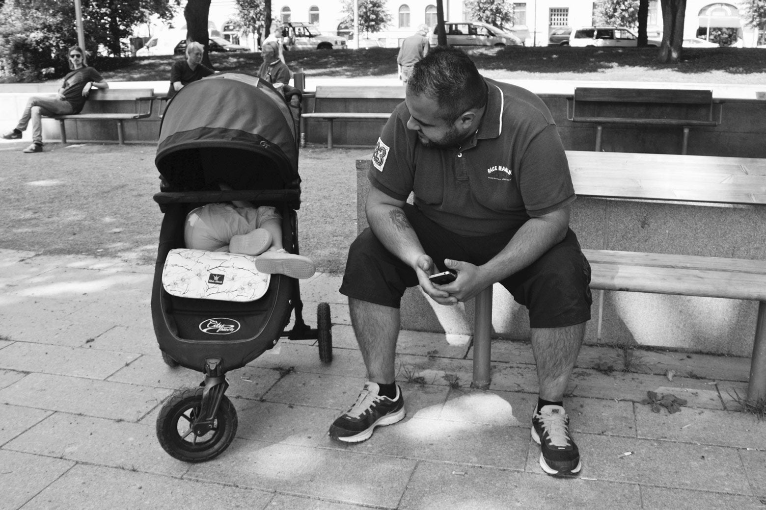 A father stops for a break on a park bench while his daughter naps in her stroller.