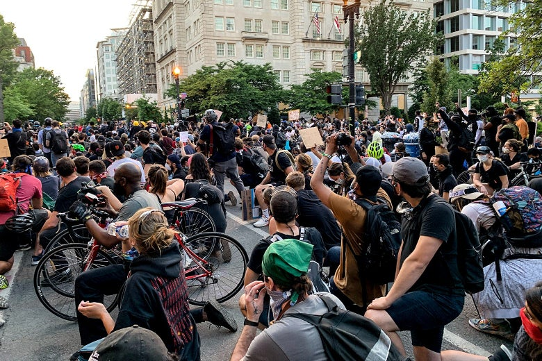 Protesters kneel in a huge crowd in the middle of the road.