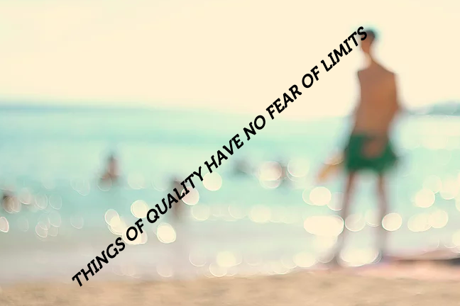 "A blurry image of someone walking on the beach with the words ""Things of quality have no fear of limits"" written in all caps, diagonally."