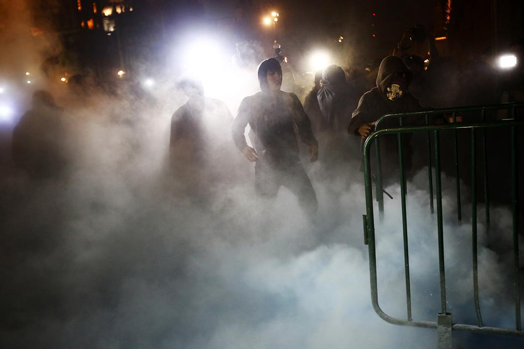 Protesters stand amidst smoke outside the palace on Nov. 8.