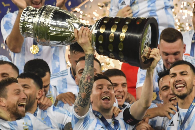 Argentina's Lionel Messi holds the trophy as he celebrates on the podium with teammates after winning the Conmebol 2021 Copa America football tournament final match against Brazil at Maracana Stadium in Rio de Janeiro, Brazil, on July 10, 2021.