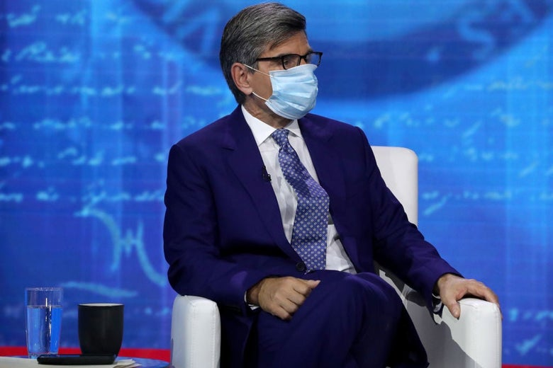 Stephanopoulos, wearing a blue suit and a medical mask, is seated onstage at a televised event against a blue backdrop.