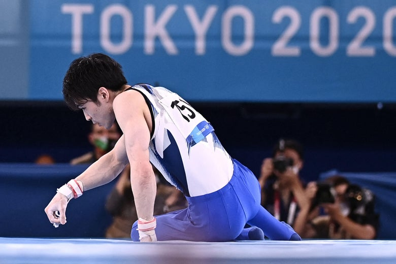 Japan's Kohei Uchimura on the mat looking to the side, a Tokyo 2020 logo in the background