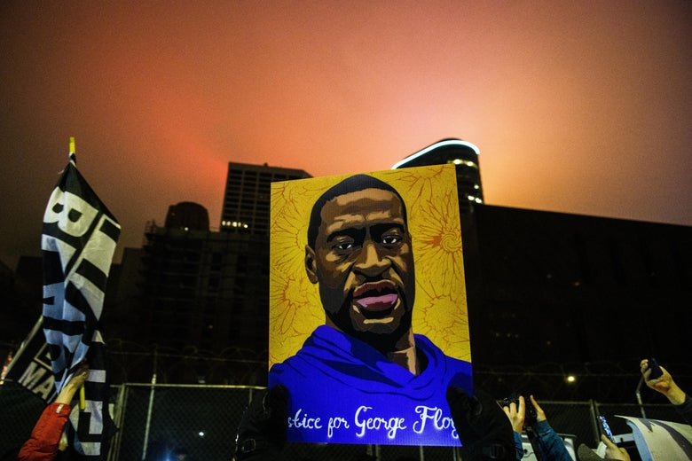 Hands hold up a painting of George Floyd in front of a building and next to a Black Lives Matter flag.
