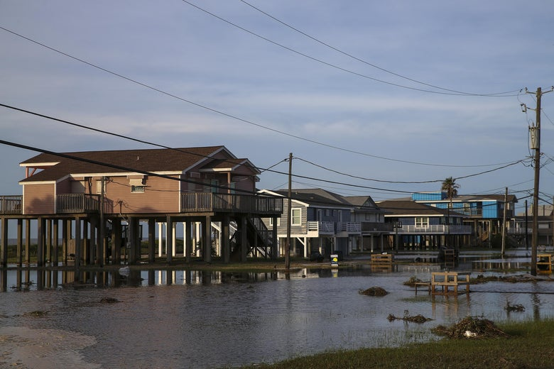 Big houses are seen behind a flooded area.