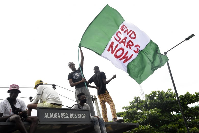 """A protester standing on top of a bus stop with others waves a giant Nigerian flag that says """"End SARS Now."""""""