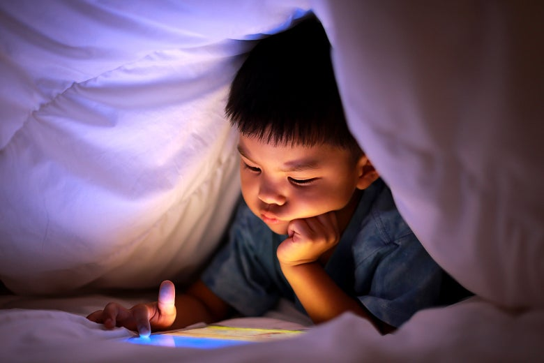 A small child uses a tablet under the covers.