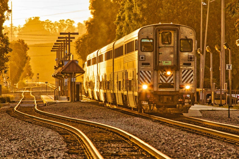 A double-decker Amtrak train in the golden hour of twilight.
