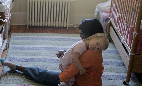 A nanny from gets a hug from the child she looks after in Brooklyn, New York.