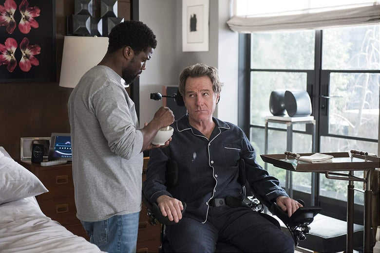 Kevin Hart holds a bowl and stands in front of Bryan Cranston, seated in a wheelchair.