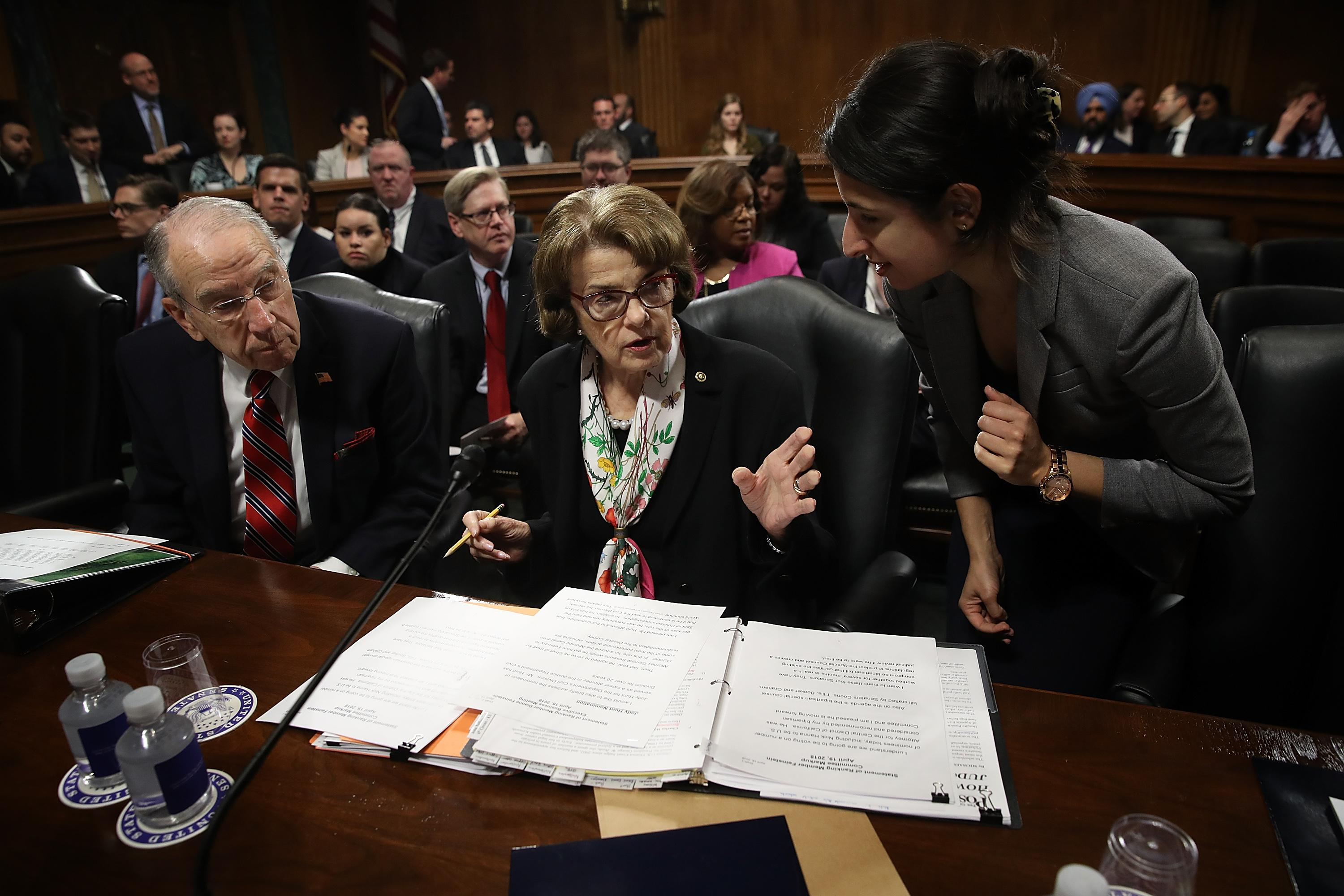 A staffer speaks to Sen. Dianne Feinstein at a committee hearing.
