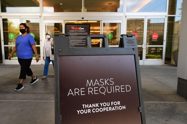 "Women wearing face masks walk out of mall doors, by a sign that says ""Masks Are Required."""