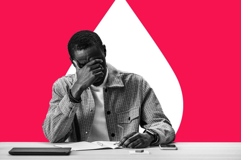A man sitting at a desk, hand on his forehead in distress.