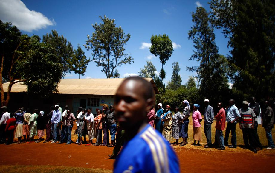 People wait in line to cast their ballots in front of a polling station in Kenya's town of Gatundu March 4, 2013.