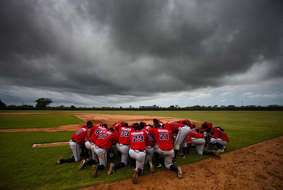 SAN PEDRO de MACORIS, DOMINICAN REPUBLIC. The Dominican Braves bow for a prayer after a game as dark clouds linger overhead. All these players have signed a professional contract with the Atlanta Braves but only the best will make the move to the US to play in the minor leagues.