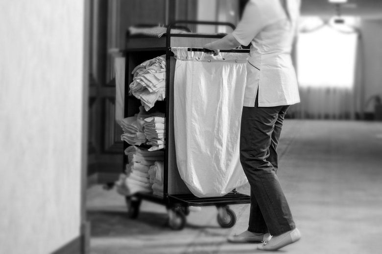 A black-and-white photo of a housekeeper pushing a cart.