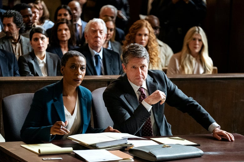 A lawyer and her client sit at a table in a courtroom.