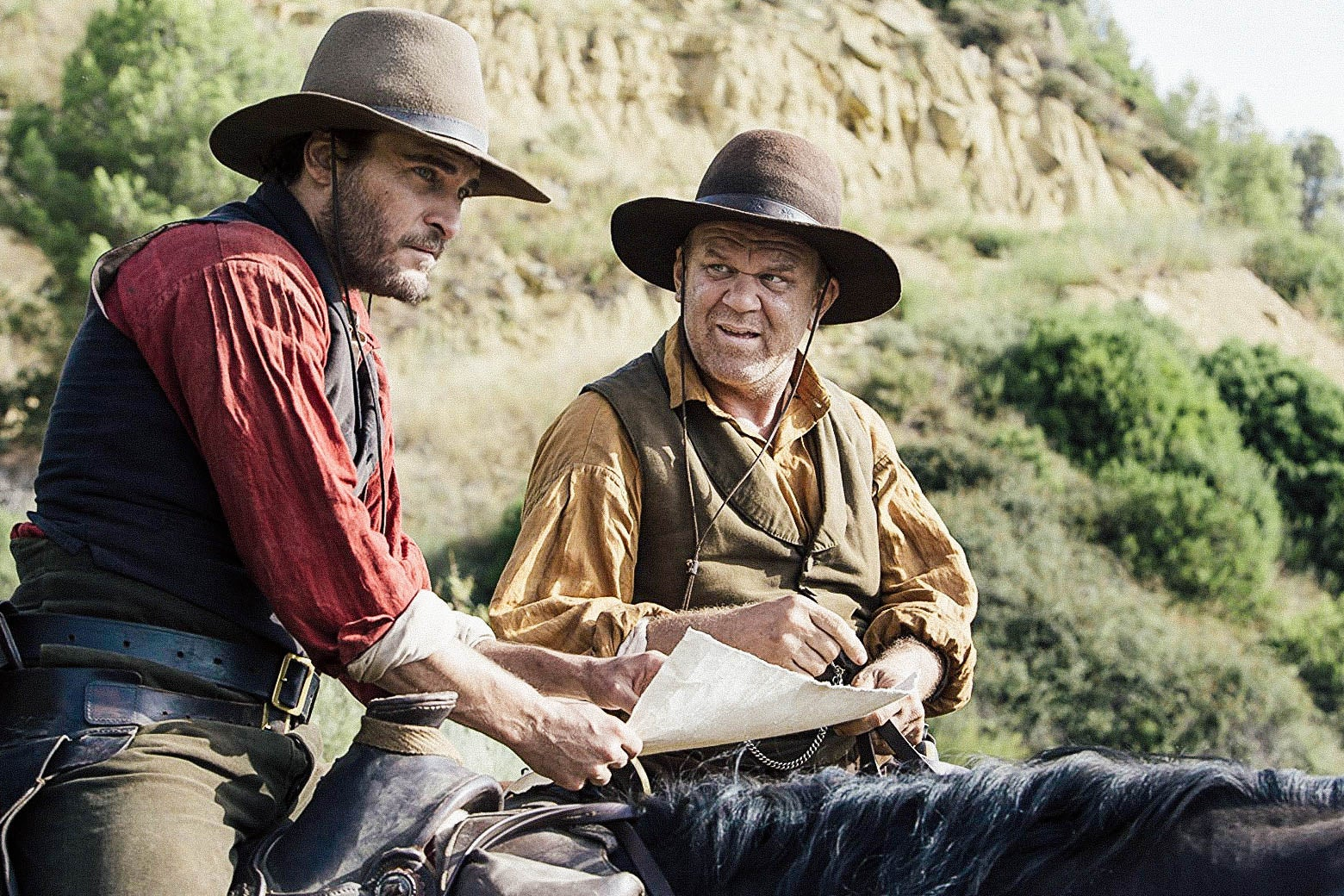 Joaquin Phoenix and John C. Reilly, both on horseback, in a still from the film.