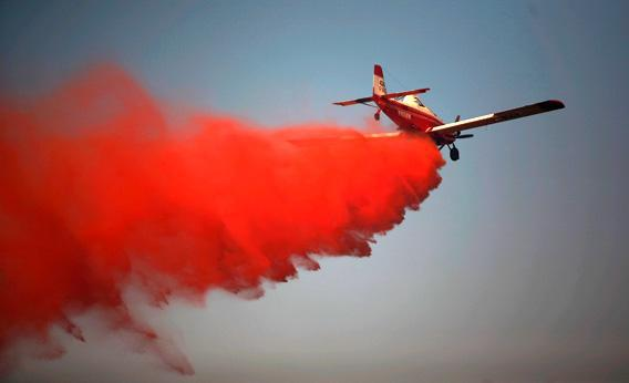 A tanker airplane drops fire retardant on a wildfire.
