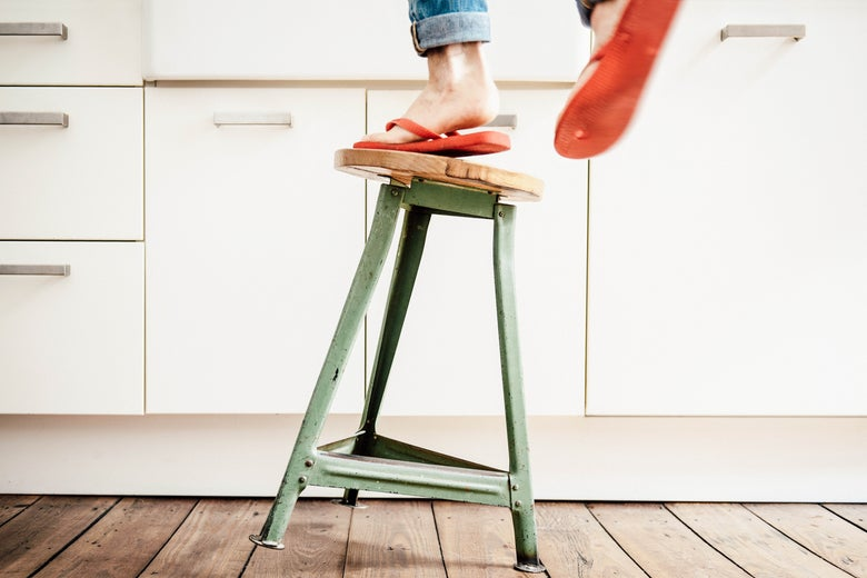 Woman in flip-flops standing on a stool that is tipping over.