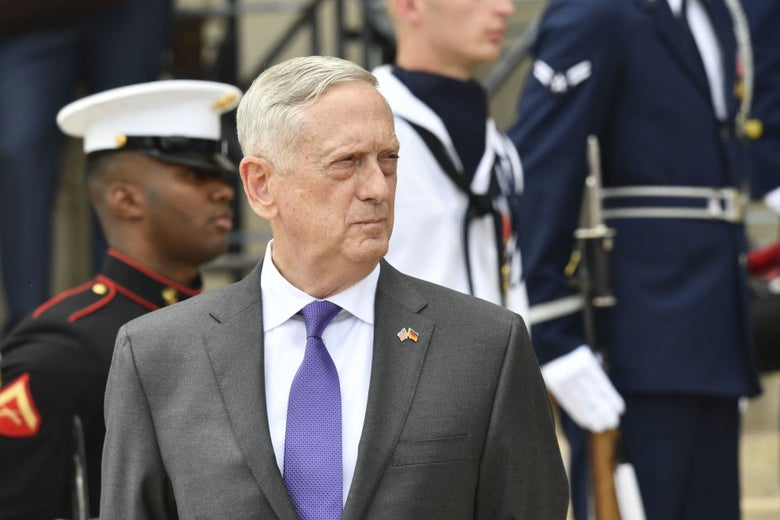 Mattis, wearing a suit and backdropped by several in-uniform service members, looks to his left.