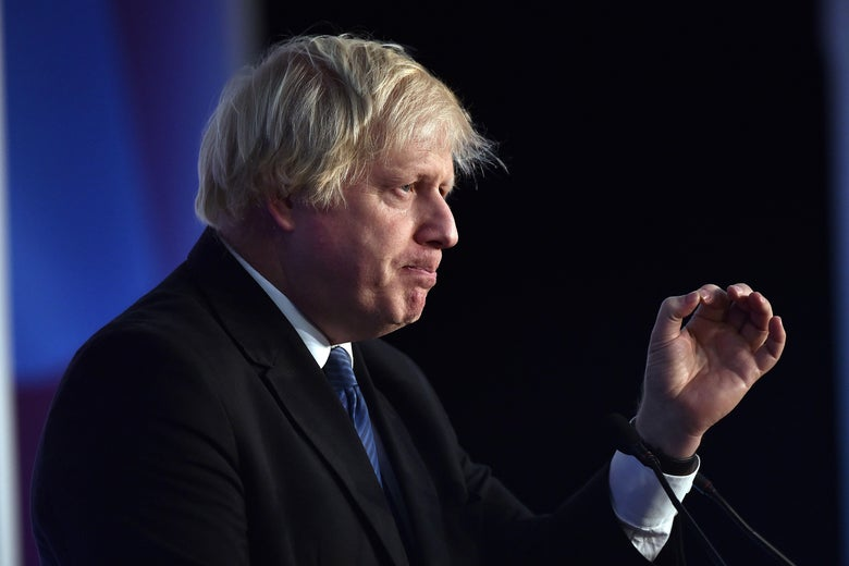Boris Johnson stands behind a podium with lips pursed and a hand in midair.