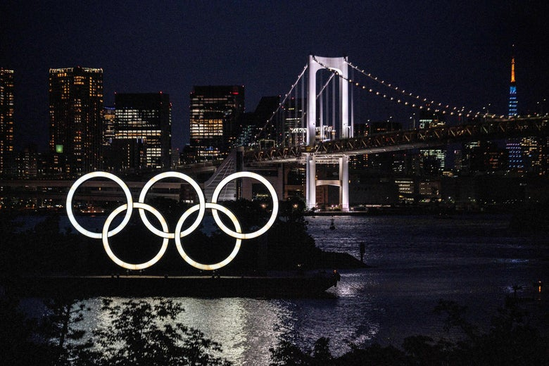 The Olympic rings are seen lit up at a waterfront, in front of a bridge and the Tokyo skyline.