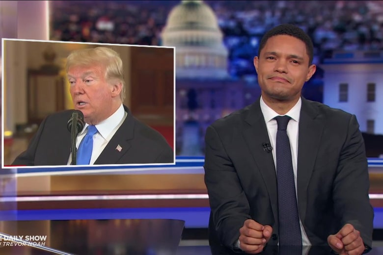 Trevor Noah in front of a photo of President Trump.