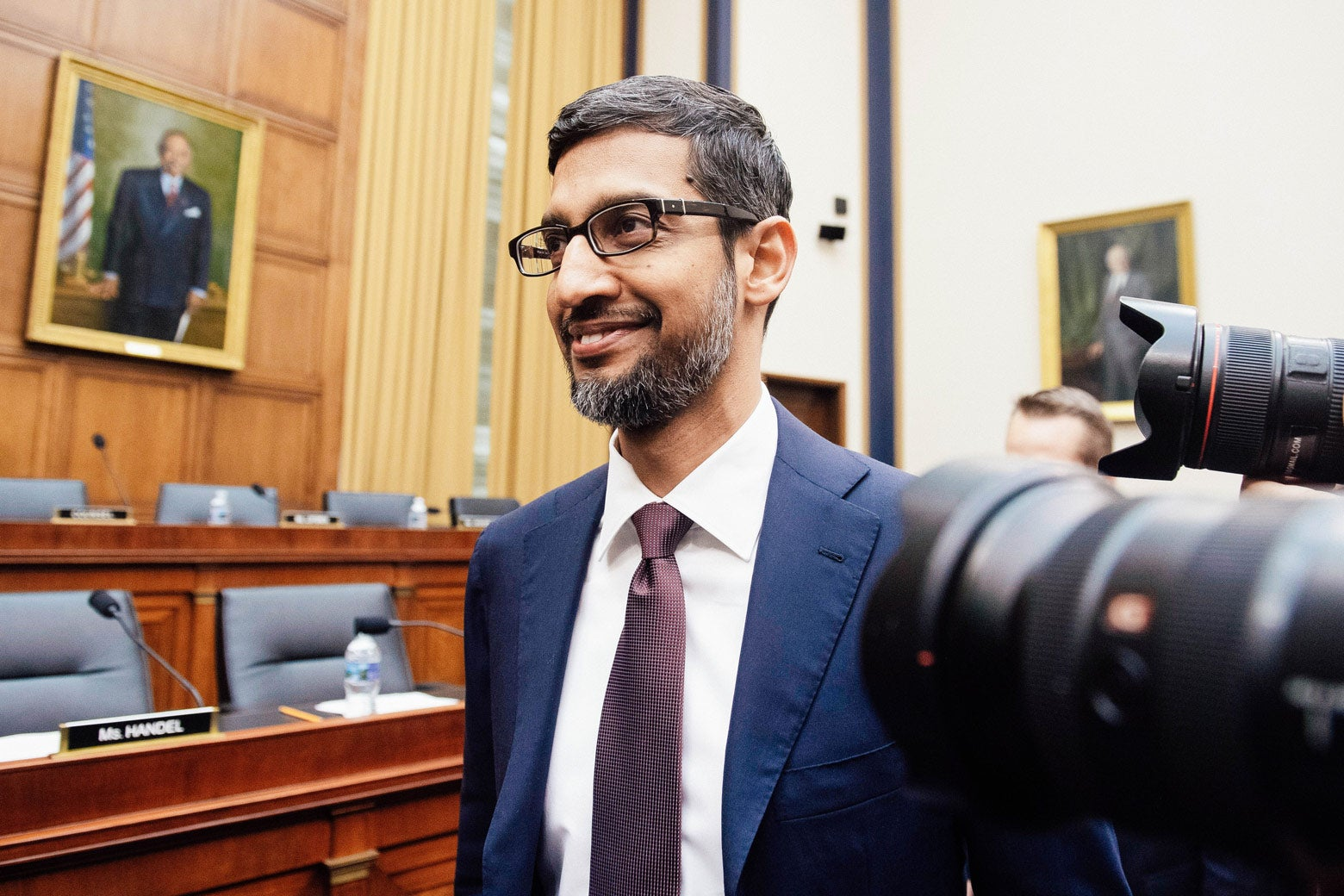 Google CEO Sundar Pichai smiles in profile for the press cameras as he arrives to testify during a House Judiciary Committee hearing in Washington on Tuesday.