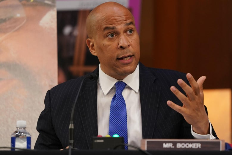 Cory Booker gestures while seated in a hearing room.