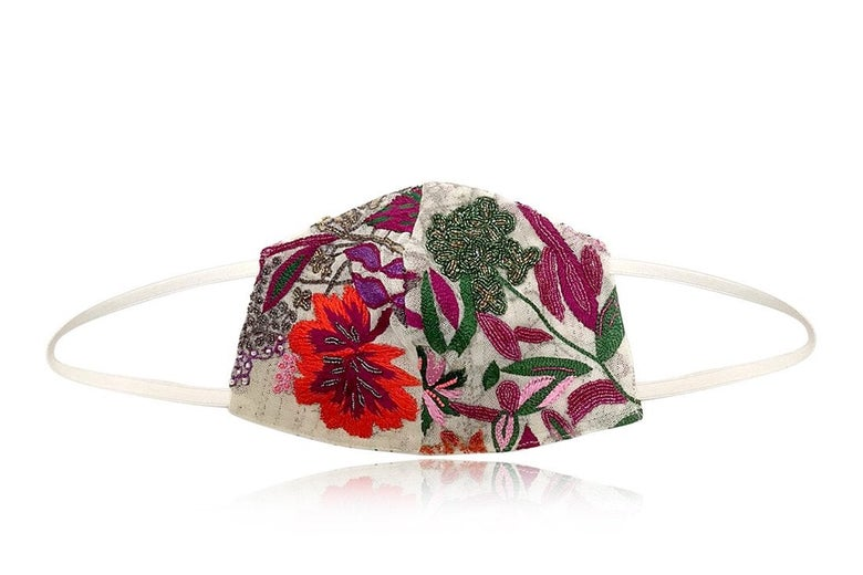 A face mask with hand-embroidered multicolor flowers and leaves on a white background