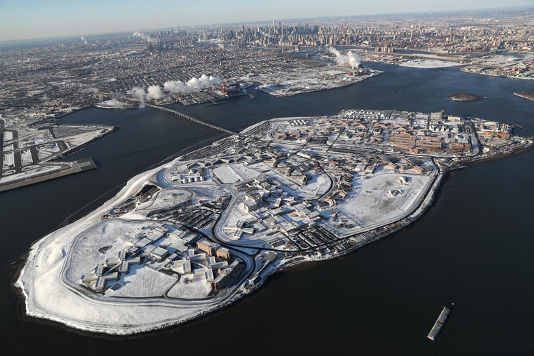 An aerial view of Rikers Island jail complex under a blanket of snow with Manhattan in the background.