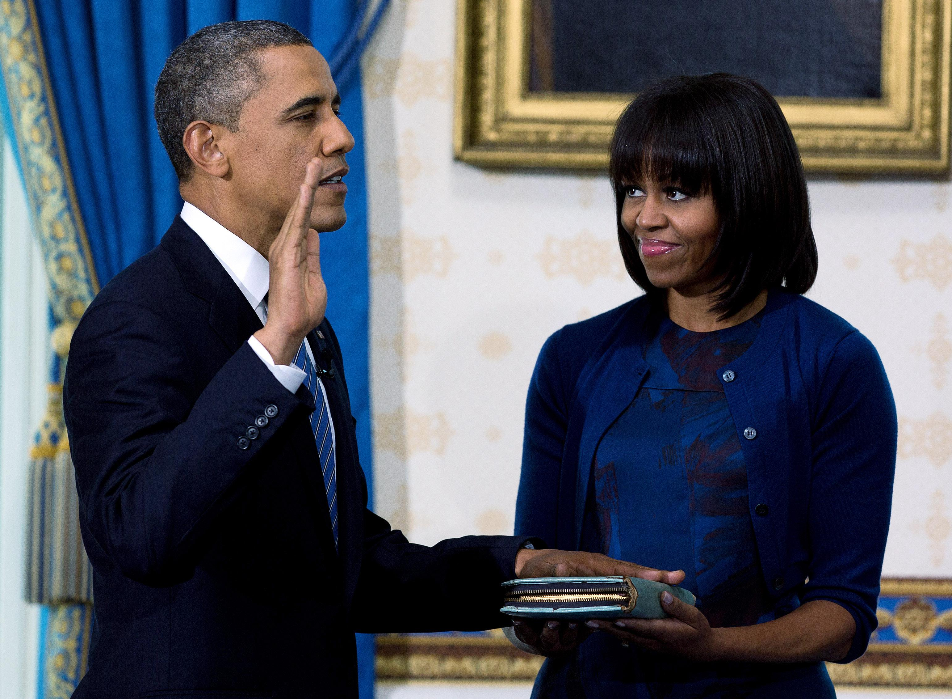 Barack Obama takes the oath of office as first lady Michelle Obama holds the Bible.