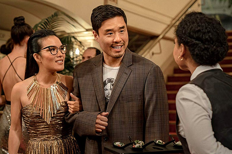 Ali Wong in a glamorous gold dress and Randall Park in an ill-fitting old suit at a party in Always Be My Maybe.