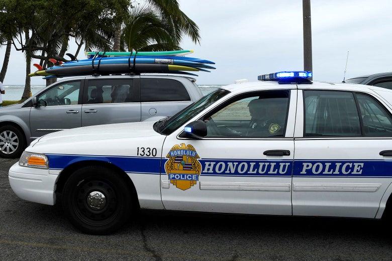 A Honolulu Police car at the beach.
