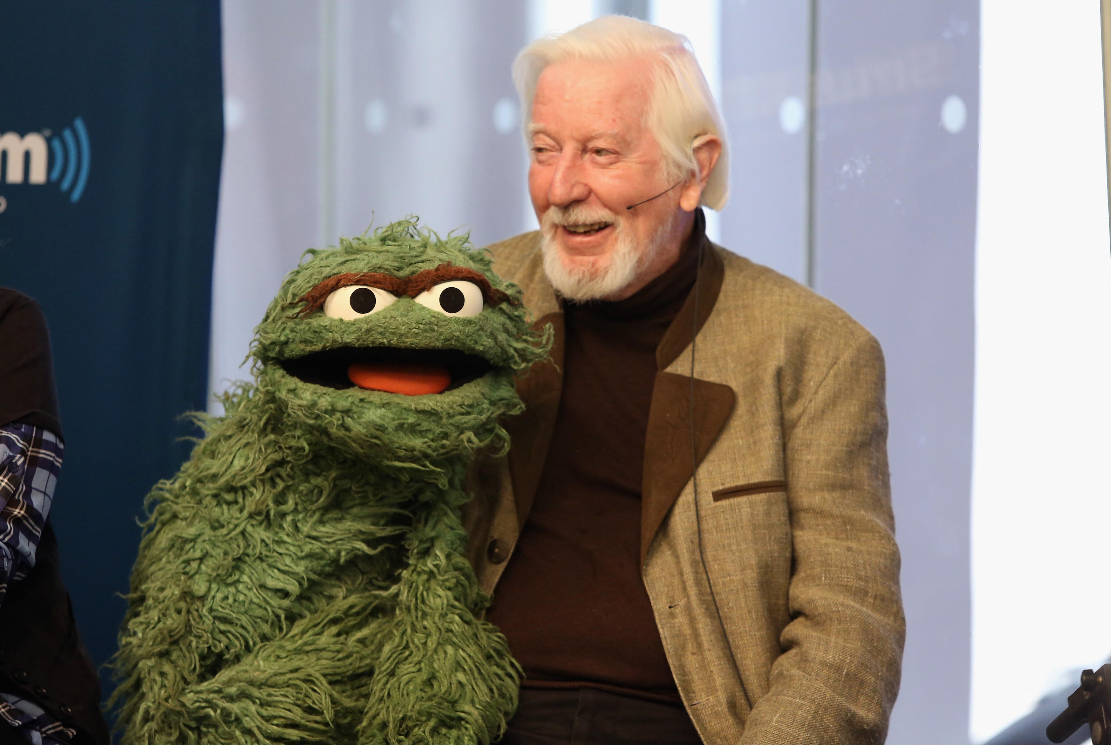 Caroll Spinney, wearing a light brown suit jacket, holds the Oscar the Grouch puppet.