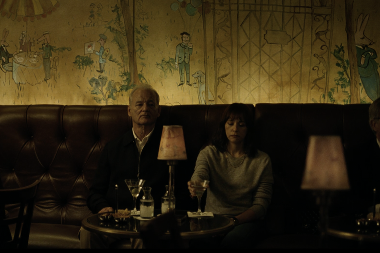 Bill Murray and Rashida Jones sit beside each other on a banquette, looking somber, with drinks in front of them, at the luxurious Bemelmans Bar in Manhattan