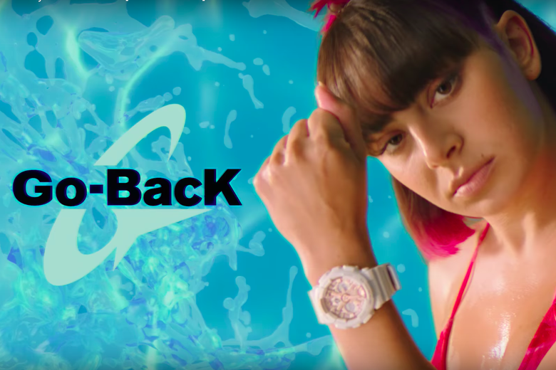Charli XCX in a pink swimsuit, brandishing a watch in front of a blue background.