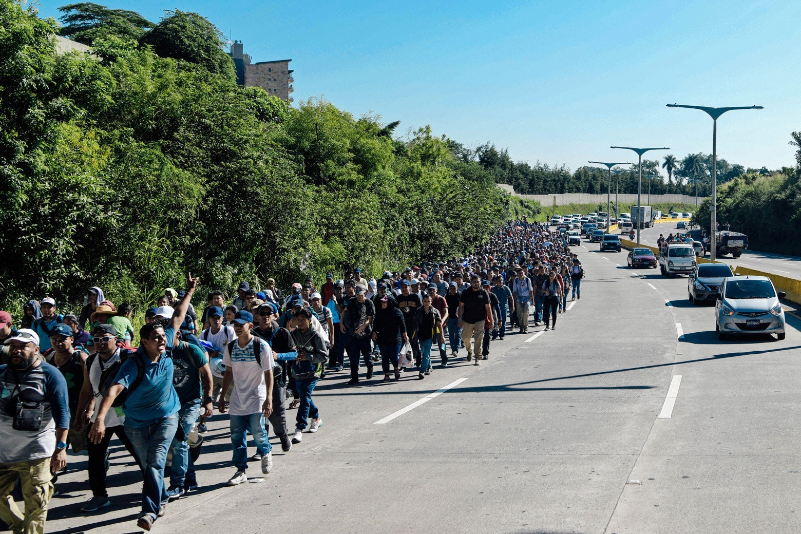 A group of migrants takes up one lane of a highway.