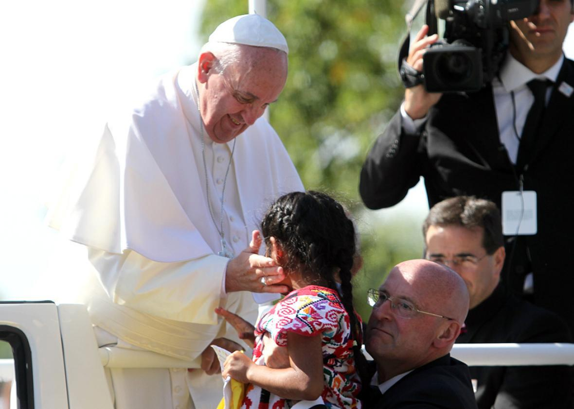 Pope Francis greets Sophie after she ran towards him during a pa