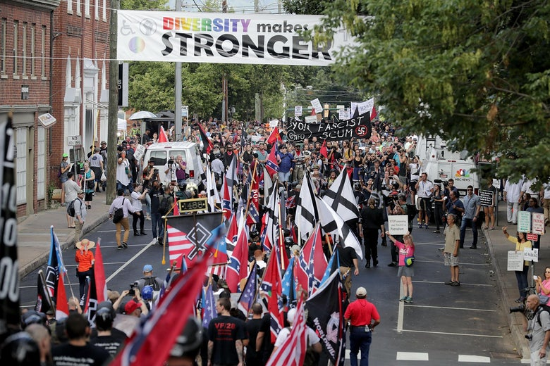 White nationalists and neo-Nazis holding flags march down a street in Charlottesville.