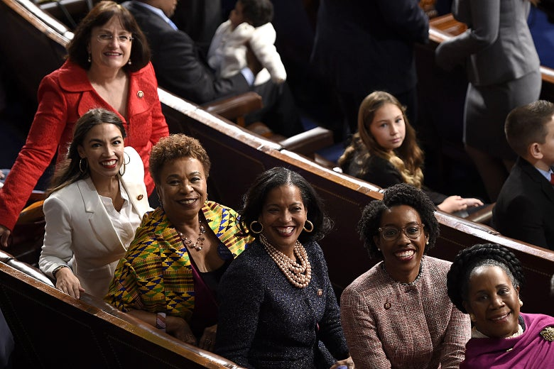 Second from left: Reps. Alexandria Ocasio-Cortez, Barbara Lee, Jahana Hayes, Lauren Underwood, and Sheila Jackson-Lee sit for a photograph on the House Chamber during the opening session of the 116th Congress on Jan. 3. A sixth women, smiling and standing to the left of Ocasio-Cortez, is unidentified in the photo.