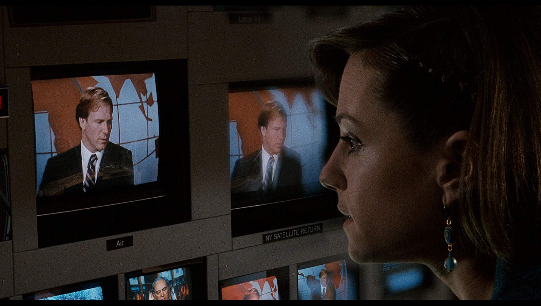 A close-up of Holly Hunter's face in a control room watching footage of anchor Willaim Hurt on several TV screens, from the movie Broadcast News.
