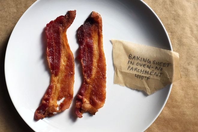 Bacon on a plate with a label: Baking Sheet in Oven - No Parchment 400 degrees F. The strips are slightly curled but mostly flat.