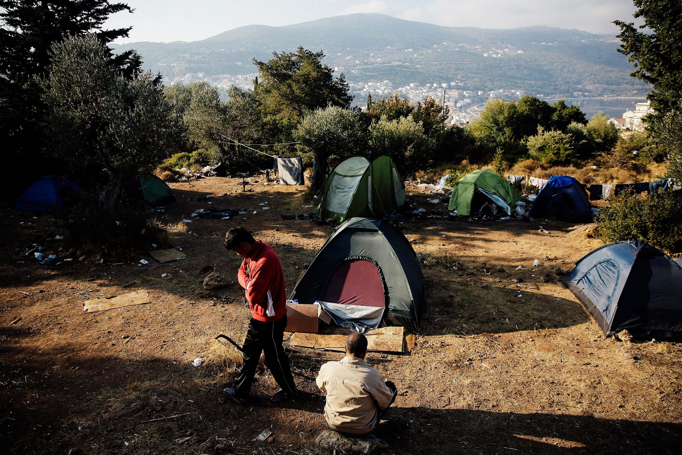 Migrants stand next to tents at a makeshift camp on the Greek island of Samos.