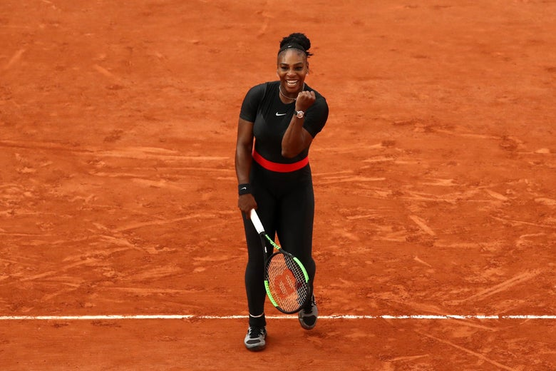 Serena Williams, wearing a black bodysuit, celebrates her victory.
