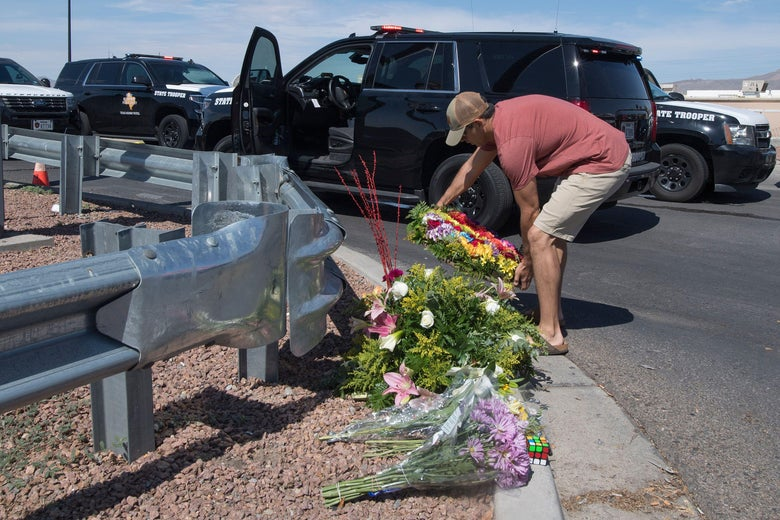 A man places flowers at a makeshift memorial on a street curb.