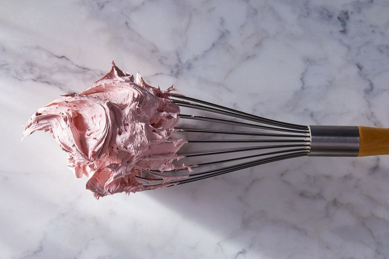 A glob of pink nougat sticks to a whisk.